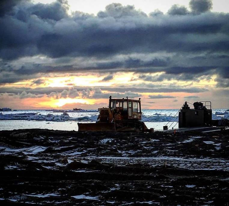 A barge and heavy equipment at dusk
